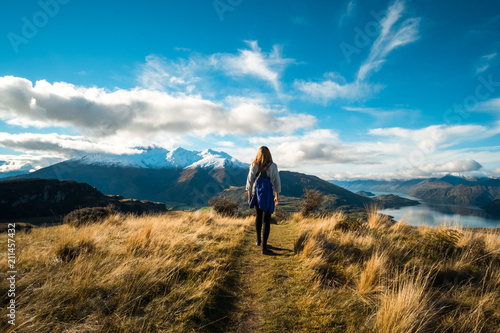 Tuinposter Blauwe jeans A hiker hiking on the beautiful track with a landscape of the mountains and Lake Wanaka. Roys Peak Track, South Island, New Zealand.