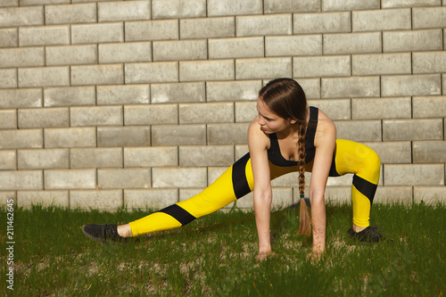 Candid shot of flexible sporty girl in black and yellow leggings