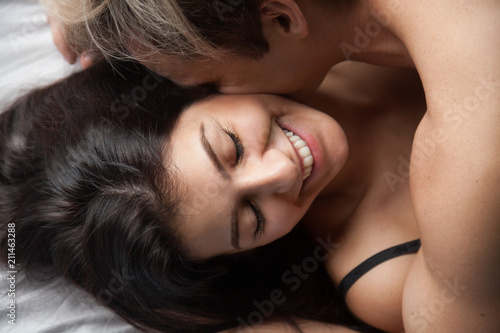 Young Smiling Woman Enjoying Intimate Romantic Moment With Beloved Affectionate Millennial Couple Lying On Bed