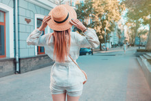 Female Fashion Concept. Outdoor Portrait Of Young Beautiful Fashionable Lady Walking On The Street. Model Wearing Stylish Hat And Clothes. Sunny Day. Back View. Waist Up. Copy Space For Text