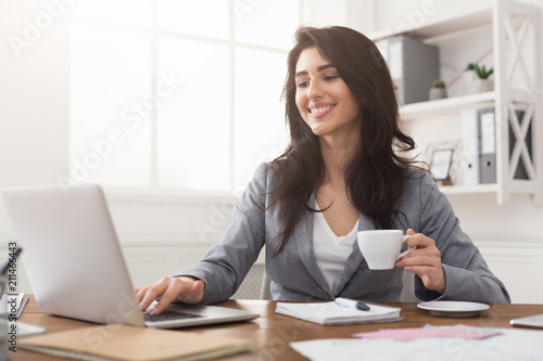 Fotografía  Smiling businesswoman working on laptop and drinking coffee at office