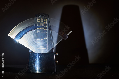 Photo metronome on a dark background, moving pendulum