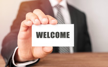 Businessman Holding A Card With Text WELCOME