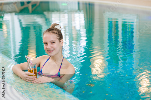Happy teen girl in the pool holding a glass of cocktail. Space for text