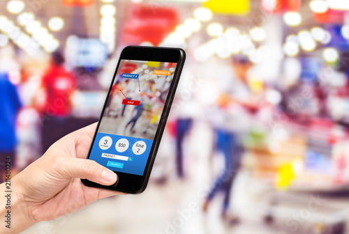 Hand hold mobile phone and using augmented reality ( AR ) app for see promotion sale in supermarket store,Digital lifestyle Technology concept.