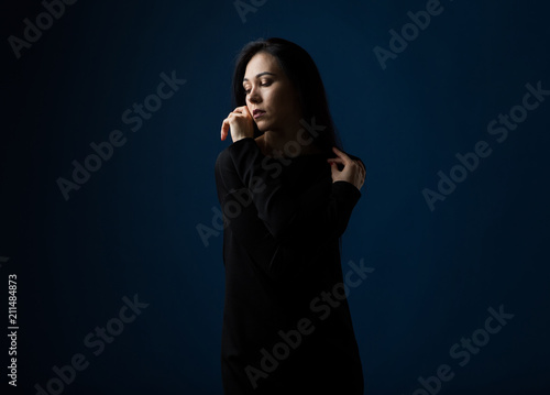 Foto  Dramatic portrait of a woman in a fashion model on a blue background