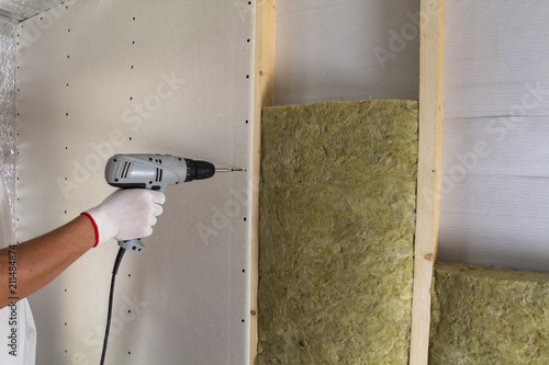 Valokuva  Close-up of worker hand with electric screwdriver fastening drywall to wooden timber frame with insulation mineral rock wool staff