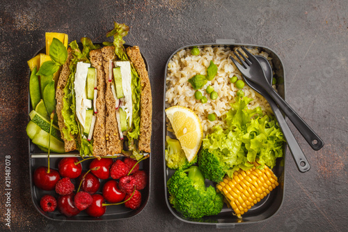 Poster Assortiment Healthy meal prep containers with feta sandwich with fruits, berries, rice and vegetables on dark background, top view.