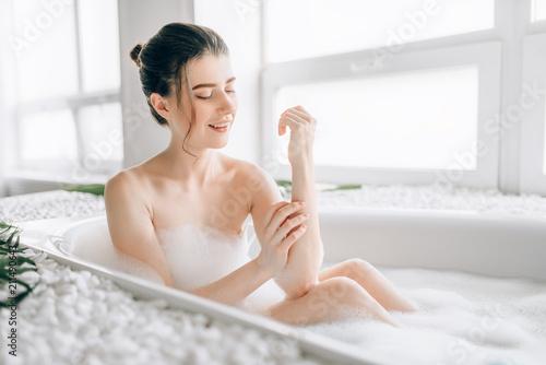 Cuadros en Lienzo Sexy woman rubs the body with foam in the bath