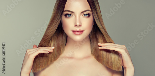 Piękna modelka z błyszczącymi brązowymi i prostymi długimi włosami. Prostowanie keratyny. Zabiegi, zabiegi pielęgnacyjne i spa. Fryzura o średniej długości. Kolorowanie, ombre i wyróżnianie