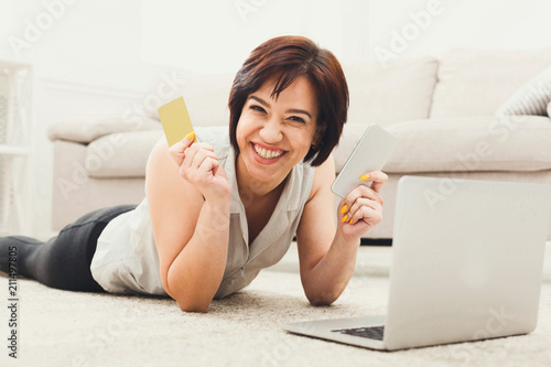 Fotografia  Happy young girl shopping online on floor