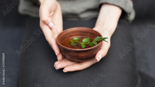 Fotografia  Herbal tea in a ceramic plate in female hands