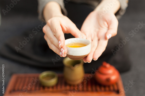 a girl in a gray linen shirt arranges a royal ceremony, classical accessories for a tea ceremony. Concept of healthy food and traditional drinks