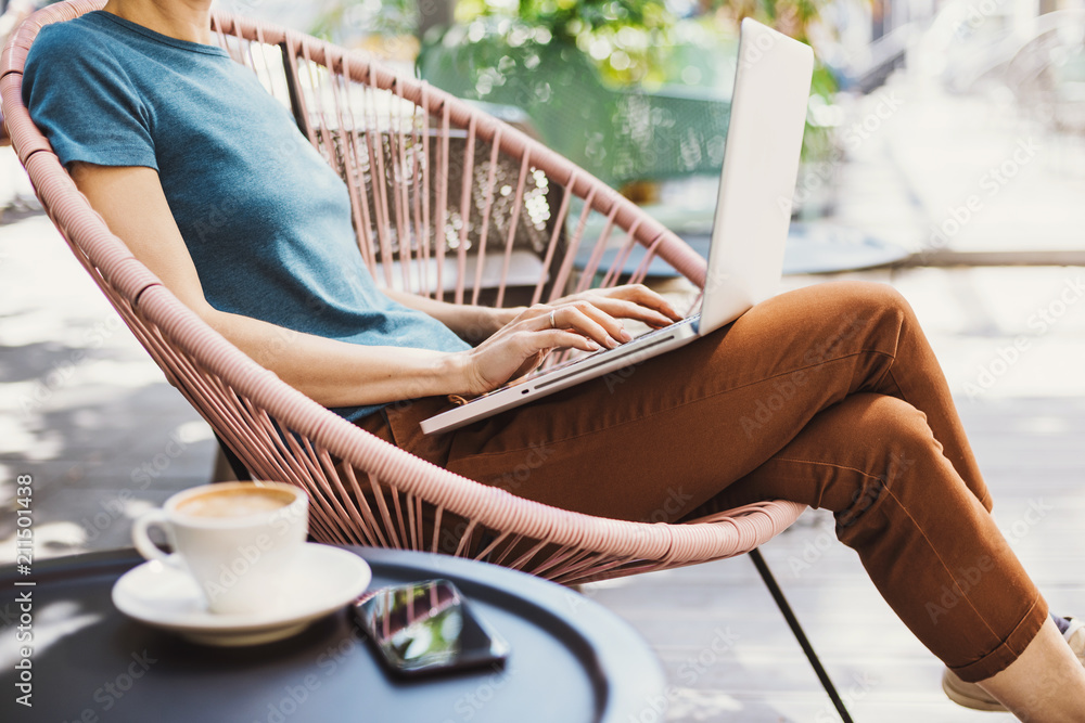 Fototapety, obrazy: Young woman using laptop outdoor. Young beautiful girl sitting in a coffee shop terrace and working on computer