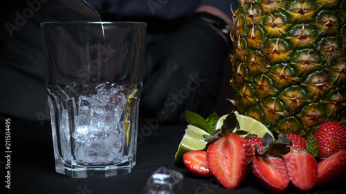 The barman makes an alcoholic drink, a pineapple, a black background.