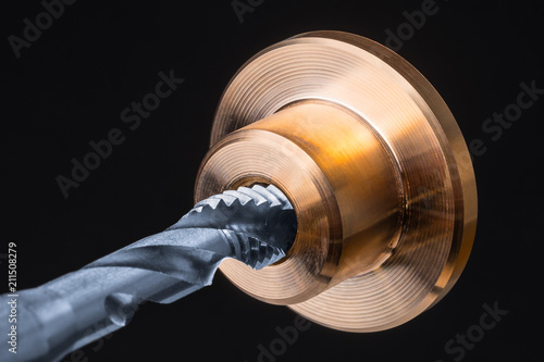 Fototapety, obrazy: Detail of spiral flute tap in golden metal part. Artistic close-up of a silver-blue steel cutting tool for threading and bronze workpiece. Tapping on black background. Engineering industry, metalwork.