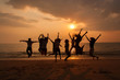 Silhouette photo of the team celebration on the beach at sunset.