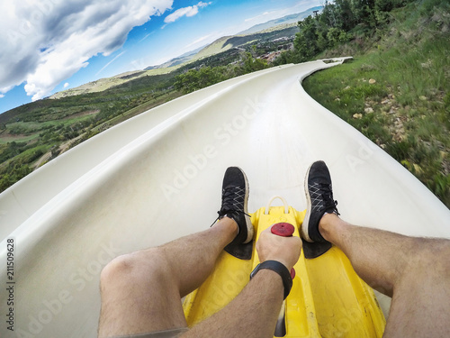 Fotografija Point of view photo of a man riding down an downhill alpine slide on a fun summe