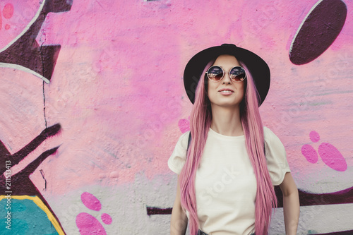 Tela Happy stylish young hipster woman with long pink hair, hat and sunglasses on the street