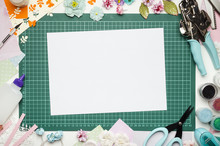 The Cutting Mat Is Surrounded By Paper Flowers, Paper, Tools And Scrapbooking Materials. Scrapbooking, Top View, White Blank Sheet In The Center