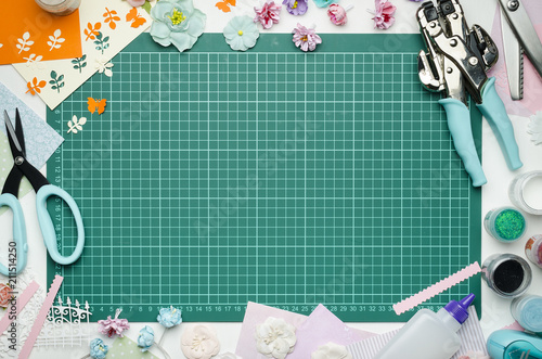 the cutting mat is surrounded by paper flowers paper tools and scrapbooking materials