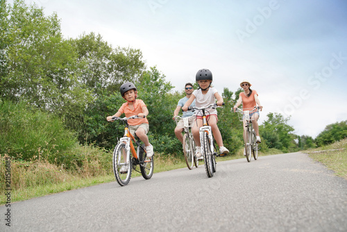 Stampa su Tela Kids with parents riding bikes in countryside