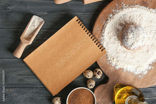 Poster Aromatische Notebook and ingredients for homemade bread on wooden table