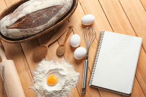 Poster Aromatische Notebook with ingredients and homemade bread on wooden background