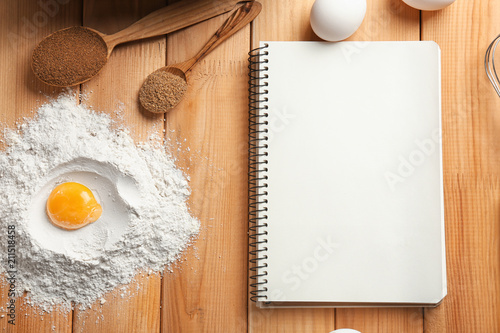 Poster Aromatische Notebook and ingredients for homemade bread on wooden background