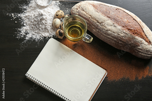 Poster Aromatische Notebook with ingredients and homemade bread on dark background