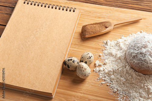 Keuken foto achterwand Aromatische Notebook and ingredients for homemade bread on wooden board