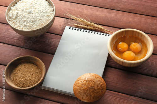 Keuken foto achterwand Aromatische Notebook and products for making bread on wooden background