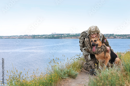 Fotografia, Obraz Man in military uniform with German shepherd dog near river