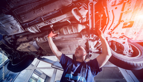 plakat Car mechanic repair car suspension of lifted automobile at repair service station