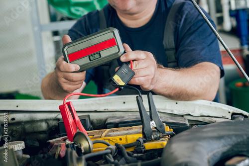 Keuken foto achterwand Vintage cars Accumulator charging. Hands and portable terminal. Car repair.