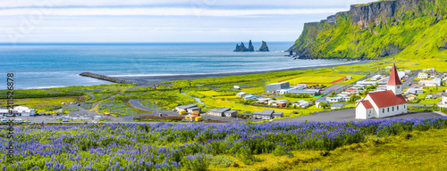 View of basalt stacks Reynisdrangar, black sand beach, church and city of Vik, I фототапет