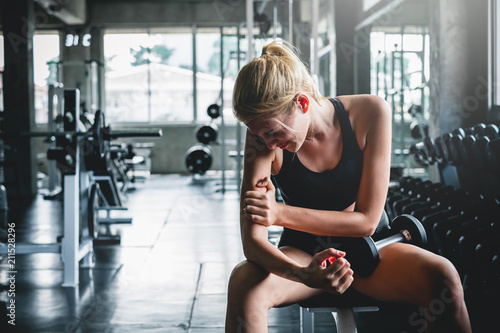 Fototapeta Woman have accident injury and hurt at arms while workout and weight training at gym, muscle pain concept obraz