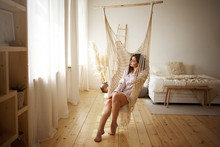 Beauty, Style, Rest And Relaxation Concept. Picture Of Fashionable Young Plus Size Female Enjoying Slow Lazy Weekend Morning At Home, Sitting Barefooted In Hanging Chair In Light Spacious Bedroom