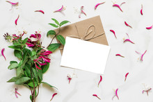 Blank White Greeting Card In Frame Made Of Pink Honeysuckle Flowers Over White Marble Table