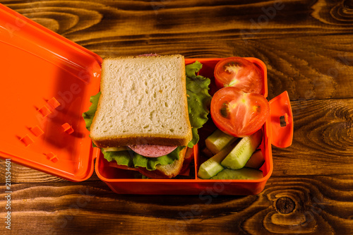 Poster Assortiment Lunch box with sandwich, cucumbers and tomatoes on wooden table