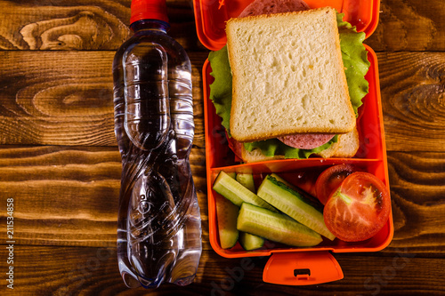 Poster Assortiment Bottle of water and lunch box with sandwich, cucumbers and tomatoes on wooden table. Top view