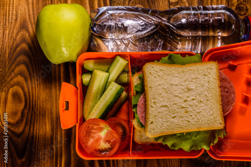 Poster Assortiment Bottle of water, green apple and lunch box with sandwich, cucumbers and tomatoes on wooden table. Top view