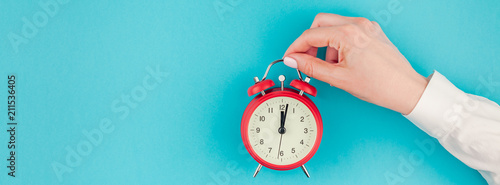 Woman hand holding the red vintage alarm clock