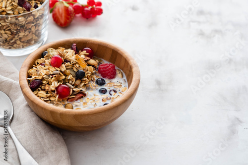 Leinwand Poster Healthy breakfast in a bowl with homemade baked granola,fresh berries, fresh strawberries and milk on a white table