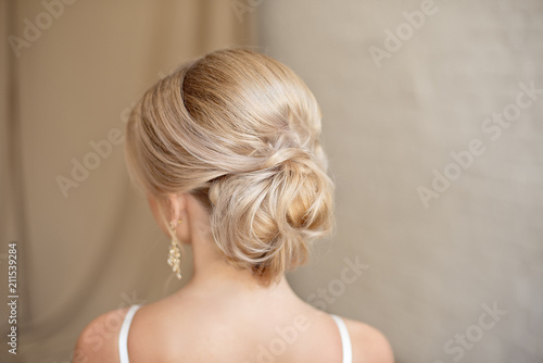 Fototapeta Rear view of female hairstyle middle bun with blond hair. obraz