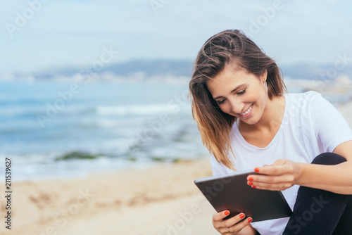 Papiers peints Kiev Young woman sitting reading on her tablet pc