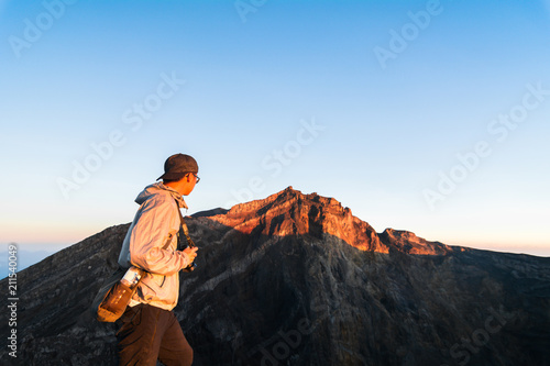 Fototapeta Asian man looking to the top of Mount Agung, the stratovolcano from the Crater Rim before eruption, Bali, Indonesia obraz na płótnie