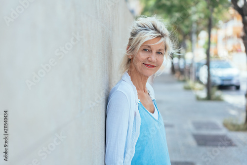 Street portrait of mature smiling blonde woman Poster