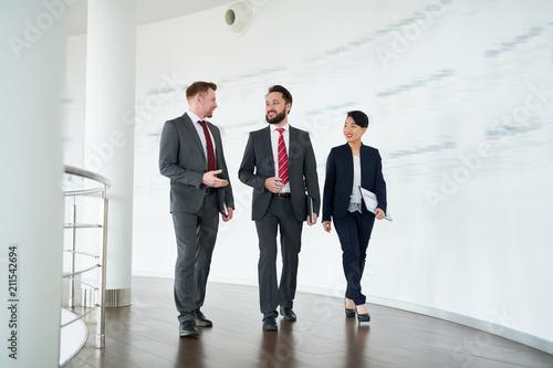 Fotografía  Business partners walking along the corridor at modern office