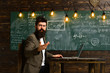 Man with long beard work on computer on chalkboard. Man in fashionable suit use laptop at school desk, new technology concept